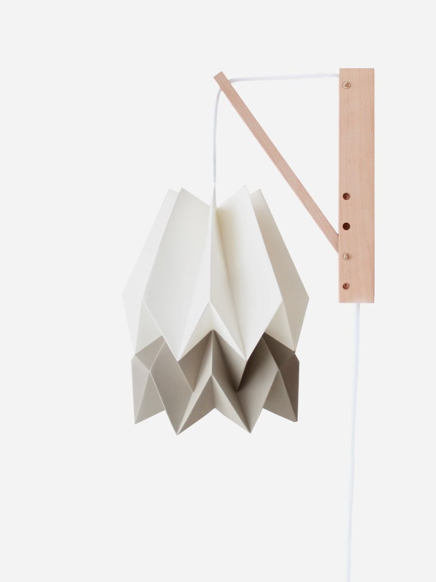Hand-crafted origami wall lamp with wooden structure and textile cable.