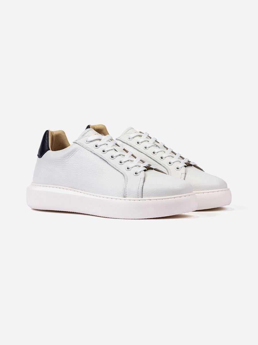 White classic sneakers with a classic cut and a navy leather detail on the heel. They are a must-have piece on the modern wardrobe.