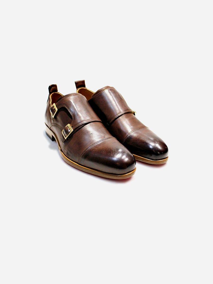 Brown shoe in leather. Closure with two metallic buckles. Decorative stitching at upper. Pull tab at back.